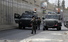 Israeli borderguards walk in front of military vehicles during clashes with Palestinian youth in the Palestinian village of al-Ram, between Jerusalem and Ramallah in the Israeli occupied West Bank, on October 22, 2015.