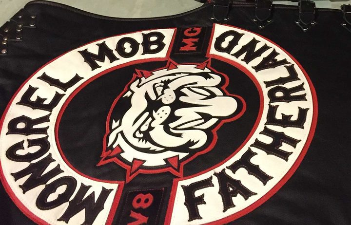 New Mongrel Mob patches on black leather  jerkins with Mongrel Mob, a bull dog and  Fatherland, lie on a table