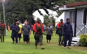 Ratu Epenisa Cakobau escorted by Police and armed military personnel.