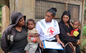 A Red Cross volunteer talks with two widows whose husbands were both killed in a landslide following the earthquake.
