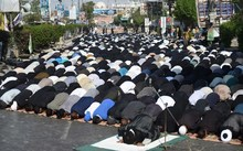 Pakistani Shiite Muslim devotees offer Friday prayers during the procession.