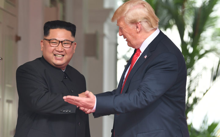 US President Donald Trump gestures as he meets with North Korea's leader Kim Jong Un at the start of their historic US-North Korea summit at the Capella Hotel on Sentosa island in Singapore