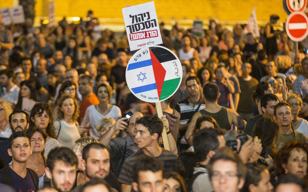 An Israeli left-wing activist holds a banner bearing images of the Israeli and Palestinian flags during a rally demanding fresh Israeli-Palestinian peace talks