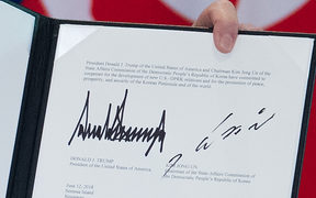The signatures of US President Donald Trump (L) and North Korea's leader Kim Jong Un (R) are seen on a document held up by Trump following a signing ceremony during their historic US-North Korea summit