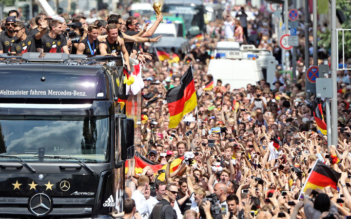 Players and members of the German national football team wave from a truck after their victory over Argentina.