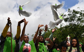 People release doves outside St Helen's church as part of commemorations on the anniversary of the Grenfell fire in West London.