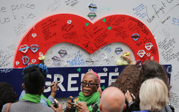 People write messages on a memorial wall near Grenfell Tower on the anniversary of the Grenfell fire in West London.