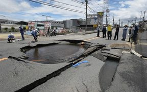 Workers stand by a partially collapsed road following an earthquake in Takatsuki, north of Osaka prefecture on 18 June, 2018.