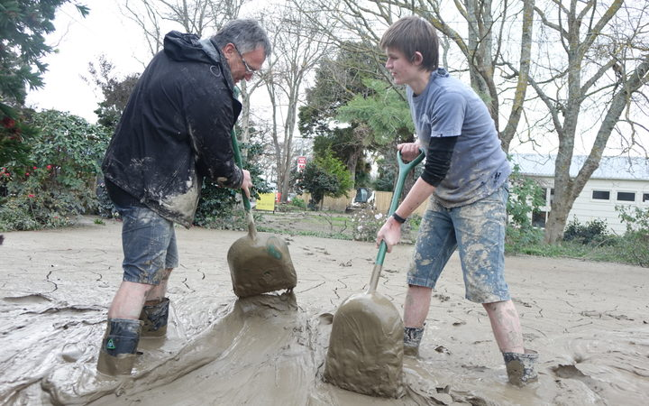 People in Whanganui work to clean up flooding at Anzac Parade.