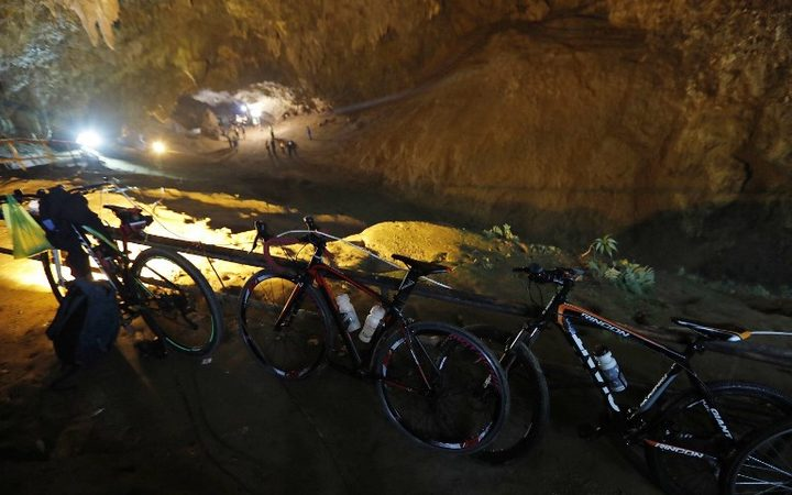 Bicycles belonging to members of a children's football team, who are trapped in a cave chamber along with their coach, are seen as Thai rescue personnel (background) conduct operations under floodlights at the entrance to Tham Luang cave at the Khun Nam Nang Non Forest Park in Chiang Rai.