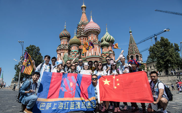 Chinese football fans of Lionel Messi, Argentina, holding flags of FC Barcelona and China, pose for photos in front of Saint Basil's Cathedral as they visit the city during the 2018 FIFA World Cup in Moscow, Russia, 17 June.