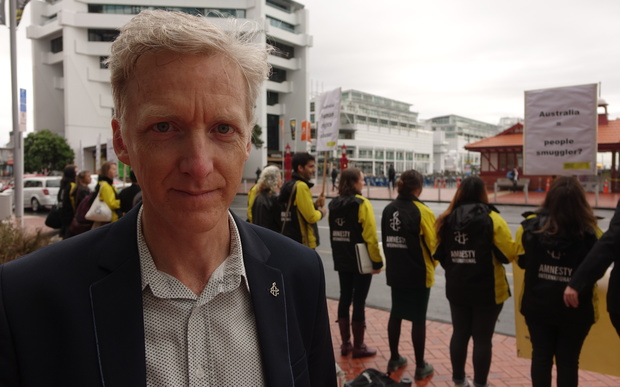 Grant Baildon stands in front of Amnesty International protesters in Auckland.