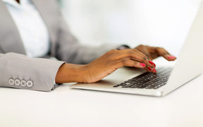 African businesswoman's hands working on laptop.