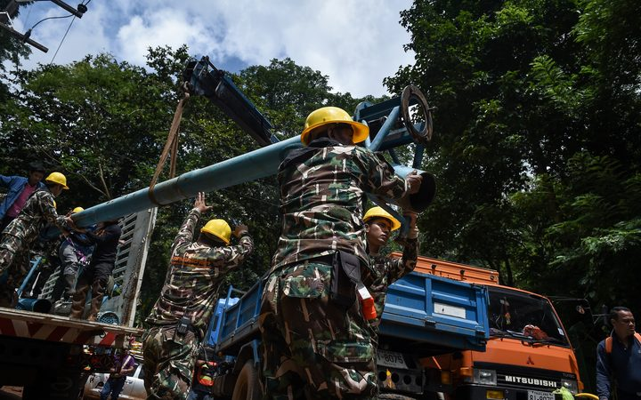 Technicians lift water pumps to the drilling site near Tham Luang cave, at the Khun Nam Nang Non Forest Park in Chiang Rai province on July 1, 2018 as the rescue operation continues for a missing children's football team and their coach.