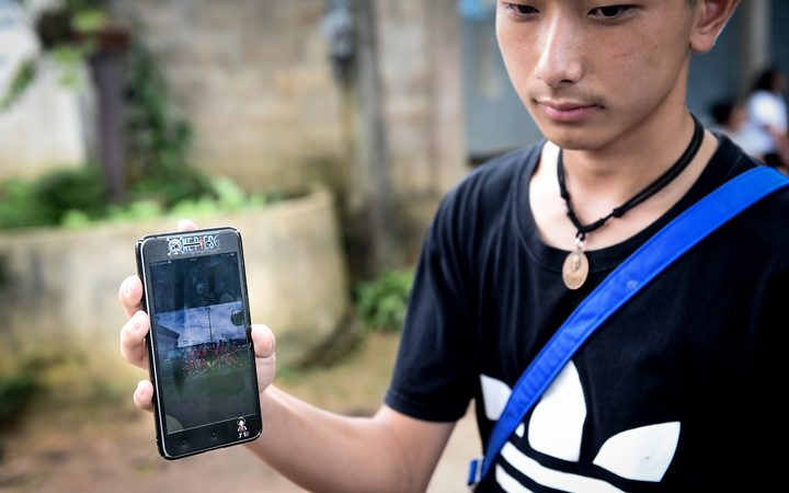 Thananchai Saengtan, 15, shows the camera a photo of his missing friends, at a football pitch near Tham Luang cave, at the Khun Nam Nang Non Forest Park in Chiang Rai province on July 1, 2018.