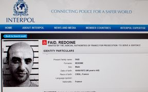 This file photo taken on April 15, 2013 in Paris shows a reproduction of the Interpol website shows the international wanted person notice for French robber Redoine Faid.
