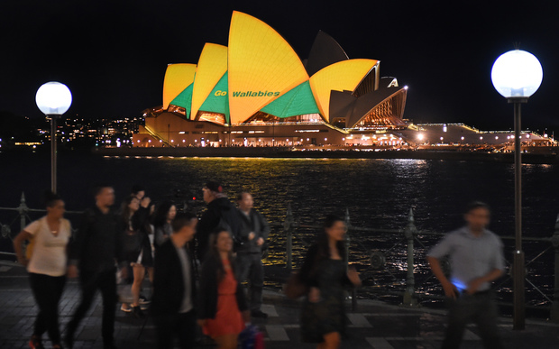People pass the Sydney Opera House lit up in Australian colours in support of the Wallabies.