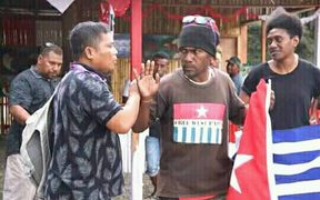 Ben Didiomea displays the West Papuan flag as Indonesian staff try  to usher him away.