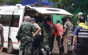 Thai soldiers and paramedics help a rescued boy on a stretcher to an ambulance outside the Tham Luang cave.