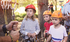 A Photo of a group of girls learning to climb on an adventure course
