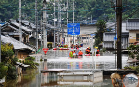 Fire fighters conduct researches at the residential area covered with water in Kurashiki, Okayama Prefecture on July 8, 2018.