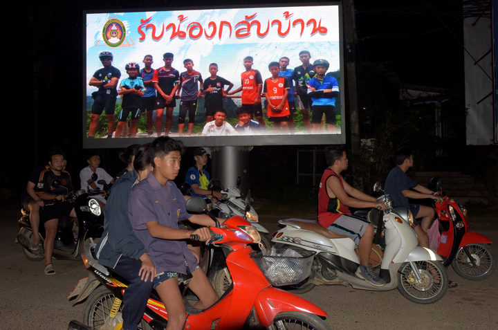 A billboard with a photograph of  members of the football team and their coach reads 'welcome home brothers'.