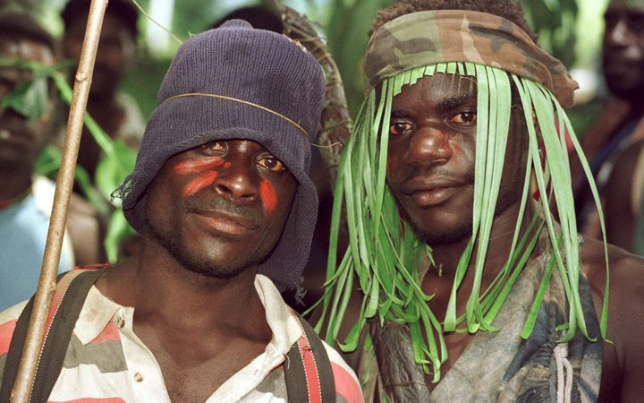 Guerillas of the Bougainville Revolutionary Army (BRA), some still wearing camouflage, watch the signing ceremony of the Bougainville Ceasefire Agreement at Arawa on Bougainville 30 April