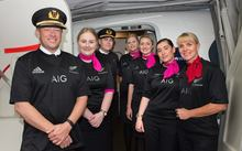 The crew on the Sydney-to-Auckland flight wearing All Blacks gear after Australia lost to New Zealand in the RWC 2015 final.