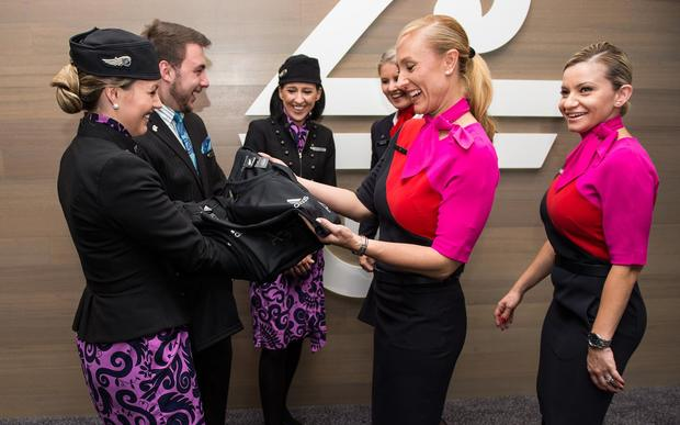 Air New Zealand crew members hand over All Blacks gear to Qantas at Sydney Airport after the Australian airline lost a wager over the 2015 Rugby World Cup.