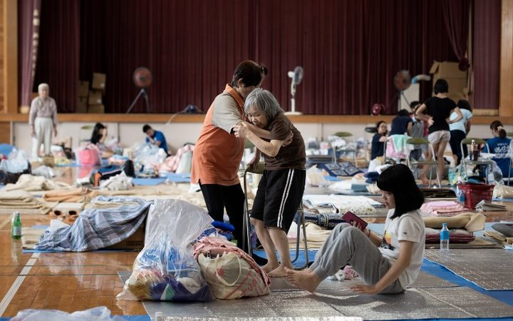 An elderly woman is given assistance as people affected by the recent flooding rest at a makeshift shelter in Mabi, Okayama prefecture on 11 July, 2018.