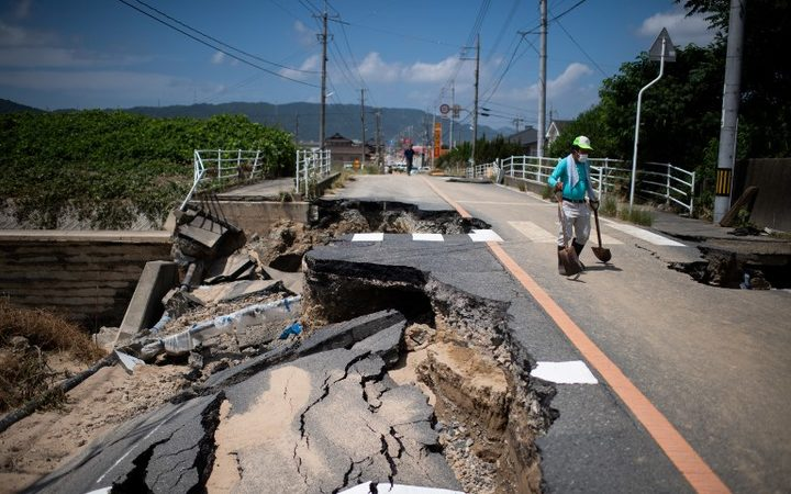 A man with a shovel walks on a damaged road in a flood hit area in Mabi, Okayama prefecture on 10 July, 2018.