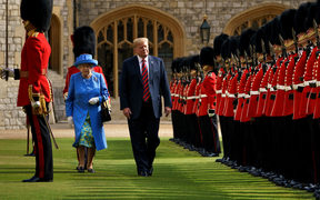US President Donald Trump is accompanied by Britain's Queen Elizabeth II as he inspects the Guard of Honour at Windsor Castle in Windsor, west of London, on the second day of Trump's UK visit.