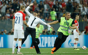 Stewards remove pitch invaders during the Russia 2018 World Cup final football match between France and Croatia at the Luzhniki Stadium in Moscow on July 15, 2018