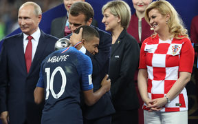 French President Emmanuel Macron embraces Kylian Mbappe at the award ceremony, with Russian president Vladimir Putin (left) and Kolinda Grabar-Kitarović, President of Croatia (right)
