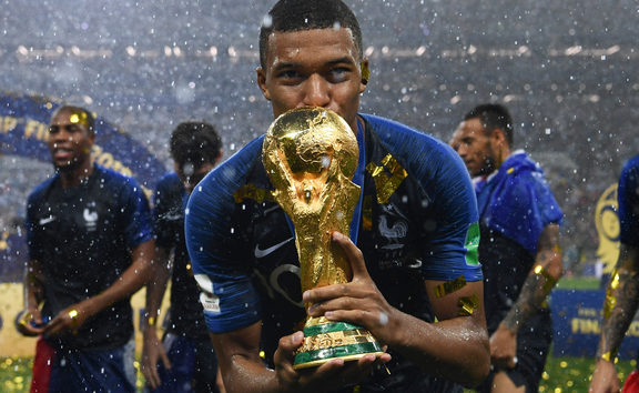 Kylian Mbappe kisses the World Cup trophy