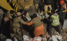 A person is carried from the debris after a factory collapsed in Lahore