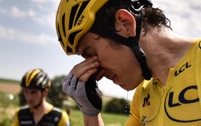 Great Britain's Geraint Thomas, wearing the overall leader's yellow jersey, cleans his stinging eyes after tear gas was used during a farmers' protest who attempted to block the stage's route.