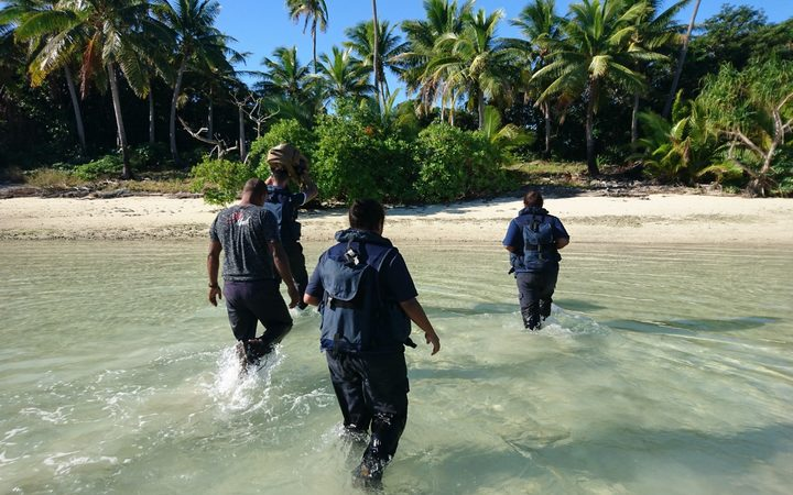 Crew members from Royal New Zealand Navy inshore patrol vessel HMNZS Taupo and personnel from Fiji Revenue and Customs Service wade towards the remote island where over 12 kgs of cocaine were found last week.