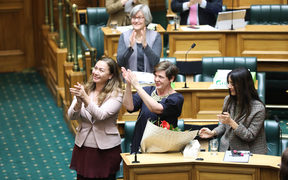 Green MPs Marama Davidson (left), Jan Logie (center) and Golriz Ghahraman  applaud Equal Employment Opportunities Commissioner Jackie Blue after the Domestic Violence Victims Protection Bill passes its third reading.