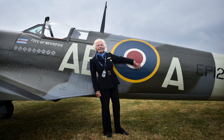 Battle of Britain veteran, pilot First Officer Mary Ellis, poses with a Spitfire aircraft.