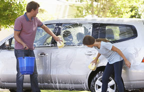 A photo of a father washing his car with histeenage daughter