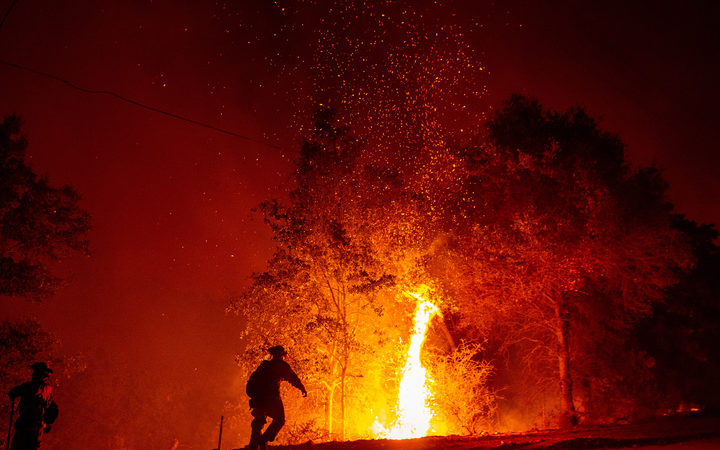 Firefighters monitor a backfire during the Carr fire in Redding, California