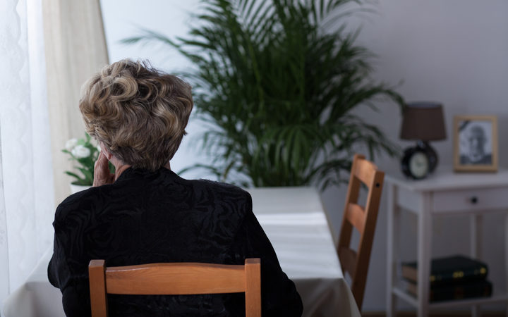 Depressed elderly widow sitting alone at home