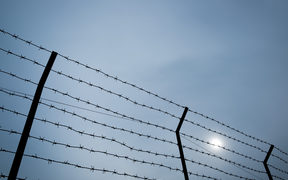 Silhouette of barbed wire on the fence of detention center.