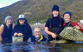 Amber McEwan (second from left) and Holden Hohaia (centre) were part of the small team that braved the wintry waters of Lake Kohangapiripiri to collect 150 kakahi.