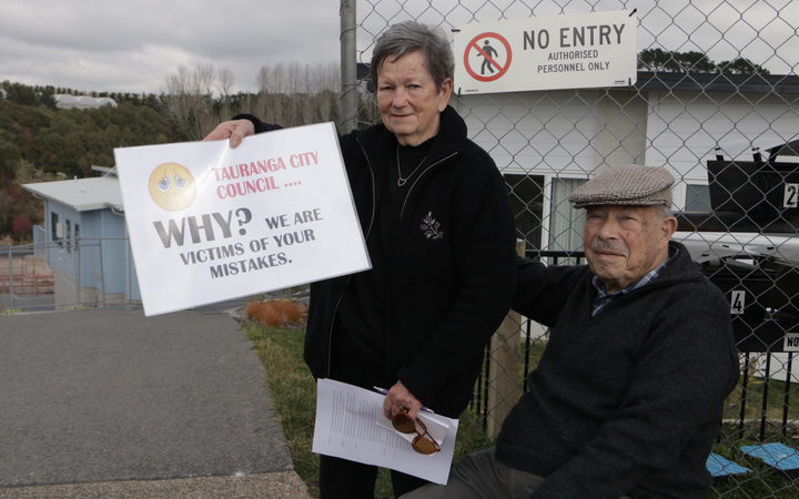 Former Bella Vista residents hold signs expressing their frustration after a compensation for the failed development was rejected.