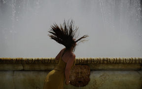 A woman refreshes herself in a fountain at Plaza de Espana, on a hot summer day in Sevilla, Spain.