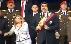 Venezuelan President Nicolas Maduro (C), his wife Cilia Flores (L) and military authorities reacting to a loud bang during a military ceremony.