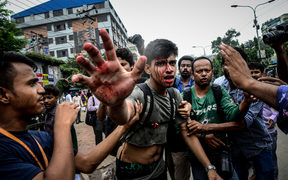 A photographer is targetted during a student protest in Dhaka.