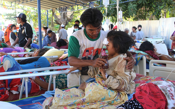 Injured victims rest at a makeshift hospital in Pemenang, the day after a 6.9 magnitude earthquake struck the area.
